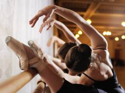 Ballerine di danza classica che eseguono esercizi alla sbarra