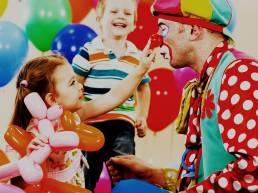 Clown animatore che intrattiene bambini durante una festa