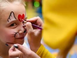Truccatrice che disegna un cuore rosso sulla fronte di una bambina