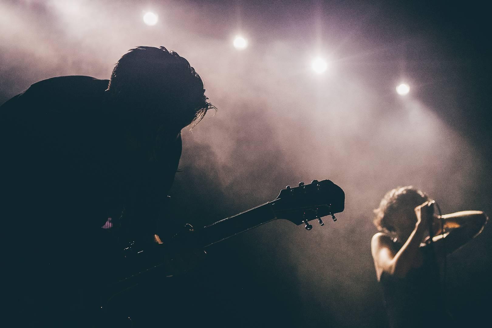 Chitarrista che suona sul palco in controluce