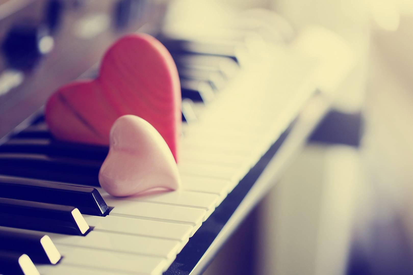 Due cuori appoggiati sui tasti di pianoforte