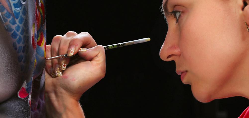 artista che dipinge sulla schiena del modello