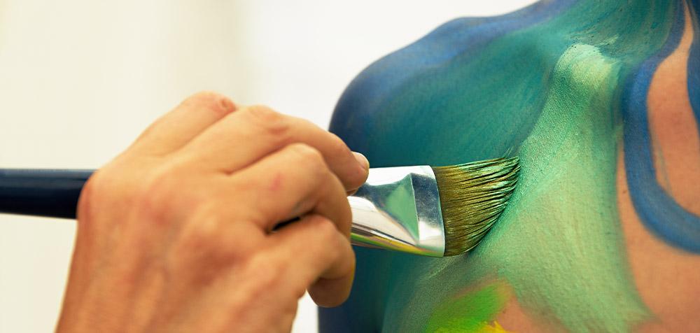 Mano di un artista con pennello che colora la spalla di una modella