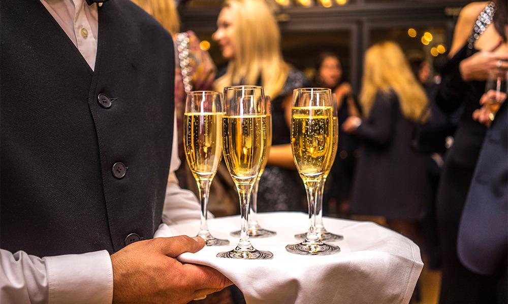 Cameriere serve bicchieri con spumante per brindisi