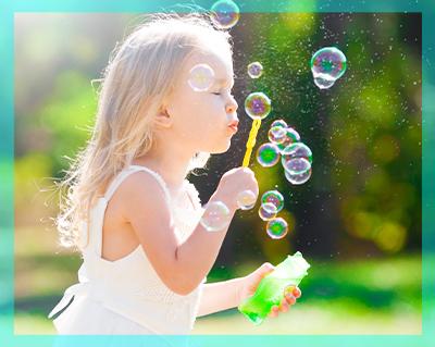 Bambina che gioca con le bolle di sapone