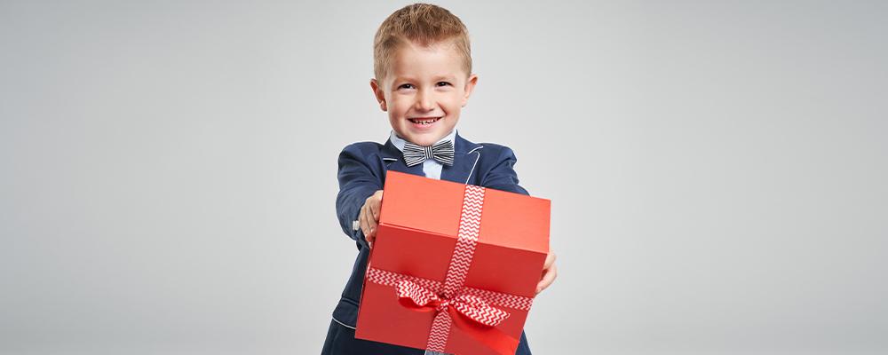 Bambino vestito elegante tiene in mano un regalo