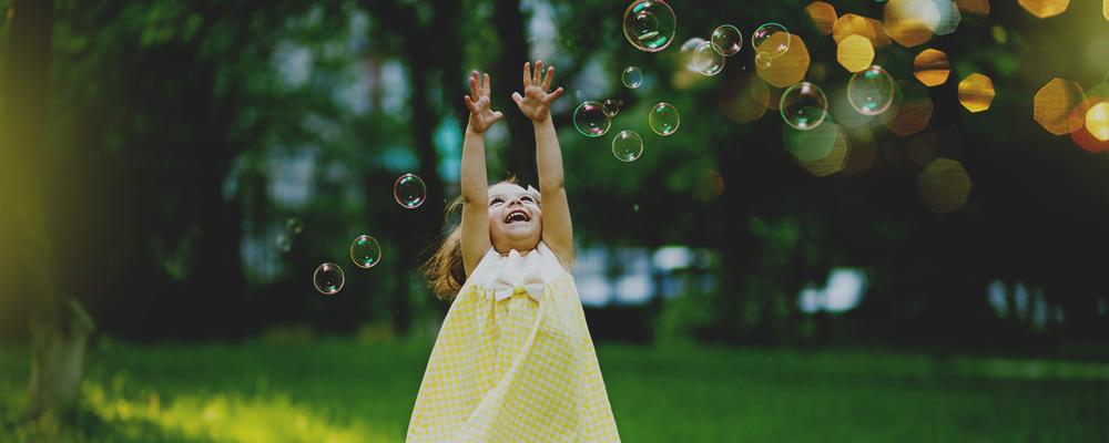 bambina gioca con bolle di sapone