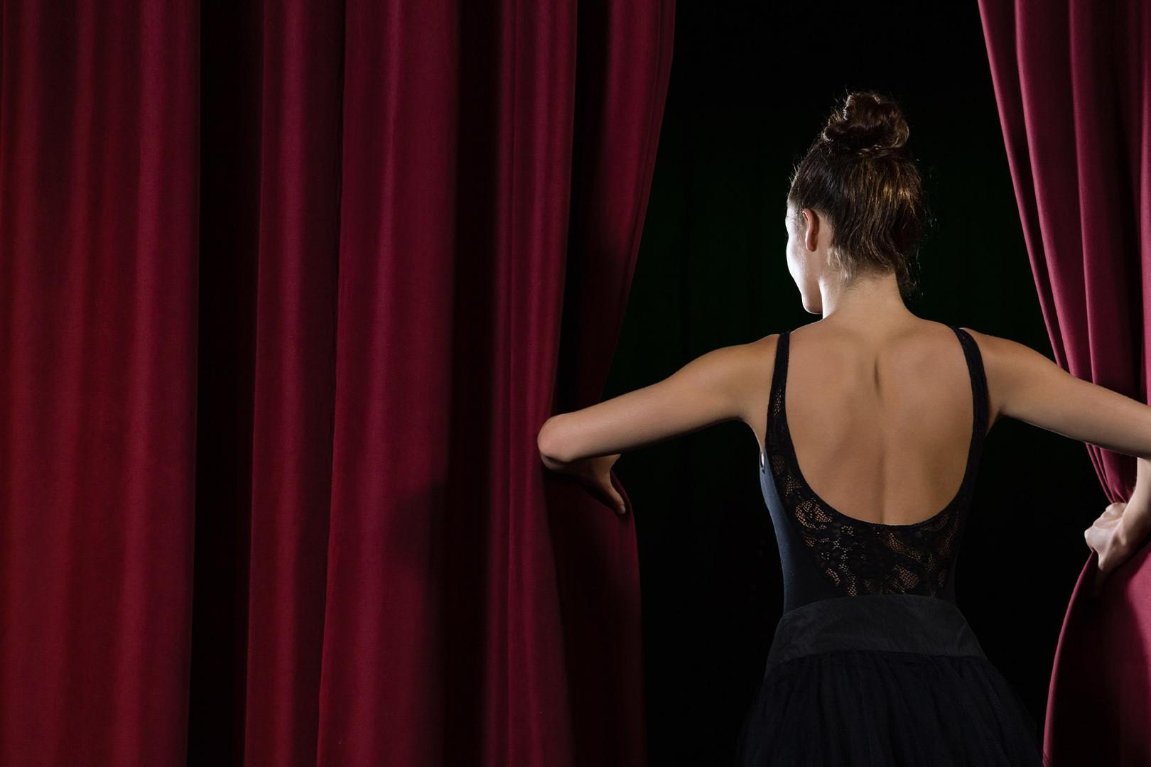 Ragazza ballerina apre il sipario per cominciare l'esibizione